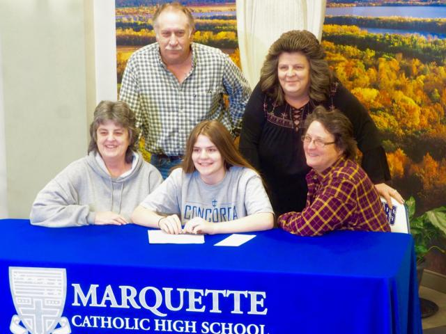 Katelyn Fitzgerald sits alongside her family members and field hockey coach, Carol Eckoff during her signing day.