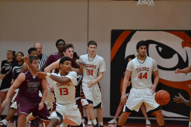 Edwardsville boys eye a loose ball in a recent contest. Edwardsville lost a close battle to East St. Louis 69-66 on Friday night.